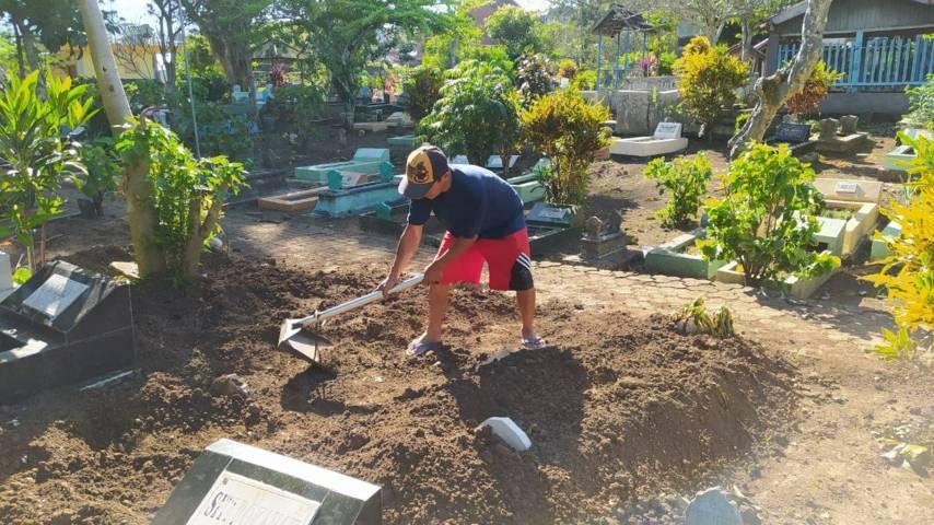 Subandi tampak menguburkan jenazah warga Sukun, Kota Malang. (Foto:Azmy/Tugu Jatim)