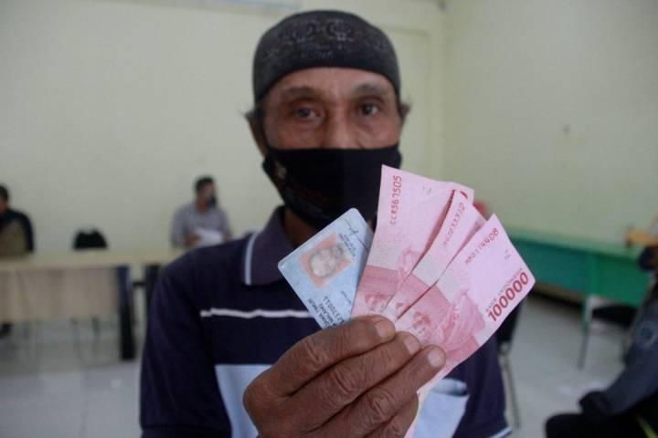 Pedagang di Kota Malang menerima uang bantuan sosial sebesar Rp 300 ribu, Sabtu (10/07/2021). (Foto: Rubianto/Tugu Jatim)