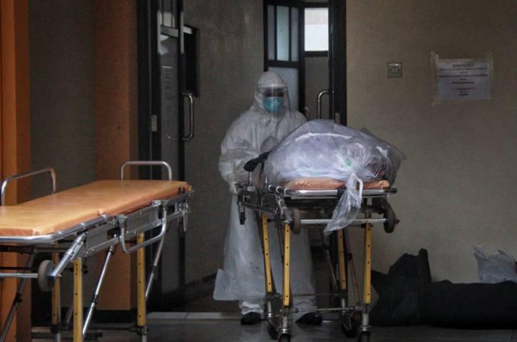 Salah satu petugas pemulasaraan mengurus jenazah Covid-19 di Kamar Mayat RSSA Malang. (Foto: Rubianto/Tugu Jatim)