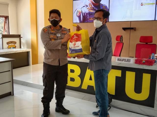 Kapolres Batu AKBP Catur C. Wibowo saat memberikan bantuan sembako kepada salah satu warga Kota Batu. (Foto: M. Sholeh/Tugu Jatim)