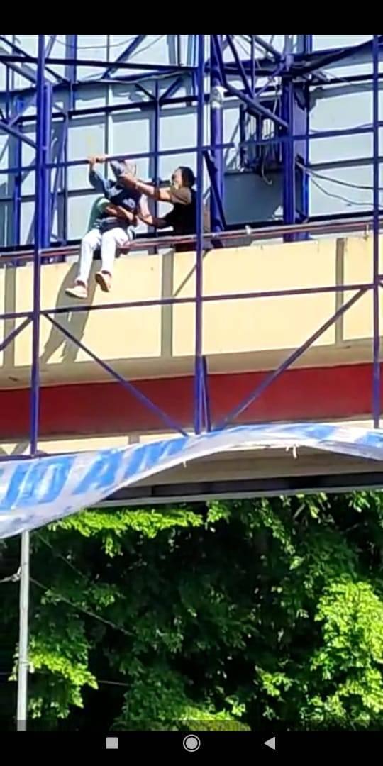 Tangkapan layar video mahasiswi cantik yang nyaris melompat dari atas jembatan penyeberangan Alun-Alun Malang. Dia berusaha dibujuk agar mengurungkan niatnya. (Foto: Dokumen/Tugu Jatim)