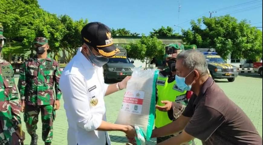 Bupati Tuban Aditya Halindra Faridzki menyerahkan bantuan beras dan masker kepada perwakilan masyarakat di Makodim 0811 Tuban. (Foto: Rochim/Tugu Jatim)