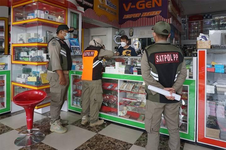 Petugas Satpol PP Kota Kediri tampak terus mengimbau pemilik di tempat usaha agar menutup sementara usahanya selama PPKM Darurat, Selasa (13/07/2021). (Foto: Rino Hayyu Setyo/Tugu Jatim)