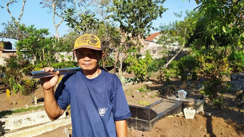 Subandi membawa peralatan untuk menguburkan jenazah di Kota Malang. (Foto:Azmy/Tugu Jatim)