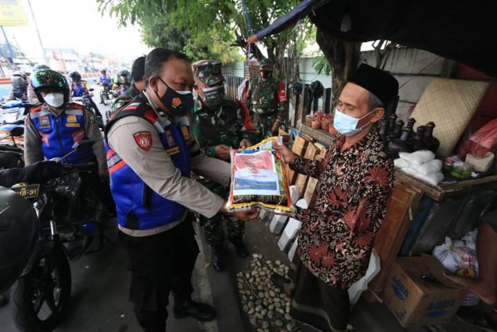 Warga terdampak PPKM Darurat dan Covid-19 merasa senang dapat bantuan sembako dari pemerintah Jatim pada Jumat (16/07/2021). (Foto: Polda Jatim/Tugu Jatim)