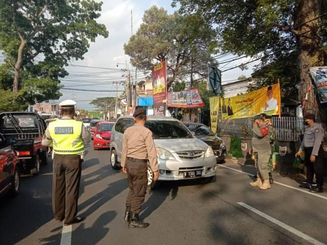 Petugas memeriksa kelengkapan syarat perjalanan bagi pengendara yang memasuki Kota Batu. (Foto:Sholeh/Tugu Jatim)