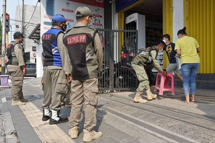 Petugas Satpol PP Kota Kediri melakukan patroli di tempat usaha warga yang tetap bandel beroperasional. (Foto: Rino Hayyu Setyo/Tugu Jatim)