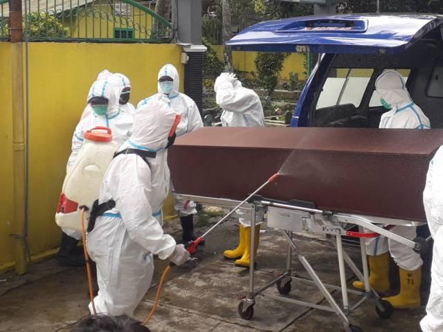 Petugas pemulasaraan di Kota Batu tampak menyemprotkan desinfektan saat akan memakamkan pasien Covid-19. (Foto: Sholeh/Tugu Jatim)