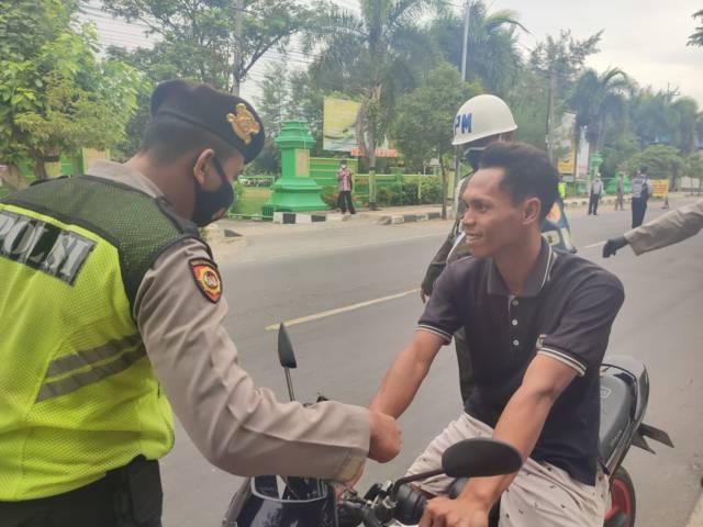 Petugas melakukan operasi yustisi di Jalan Nasional Deandles, tepatnya di depan Kantor Kecamatan Palang, Tuban, Jumat (16/07/2021). (Foto: Humas Polres Tuban/Tugu Jatim)