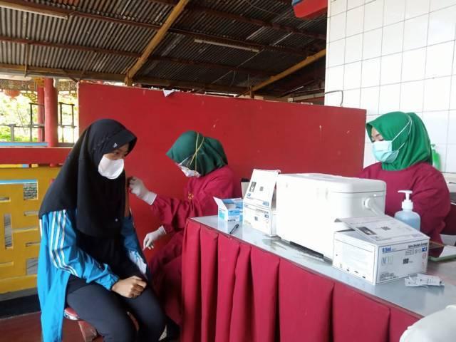 Proses vaksinasi kepada Jacinda Nabil Nur Faizah oleh vaksinator di Tempat Ibadah Tri Darma (TITD) Kelenteng Kwan Sing Bio Tuban, Kamis (15/07/2021). (Foto: Rochim/Tugu Jatim)