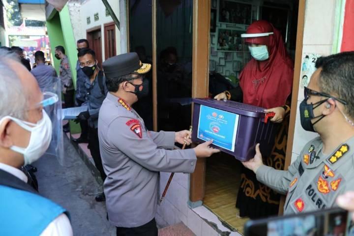 Panglima TNI Marsekal Hadi Tjahjanto dan Kapolri Jenderal Listyo Sigit Prabowo memberikan bantuan kepada warga, Jumat (16/07/2021). (Foto: Polrestabes Surabaya/Tugu Jatim)