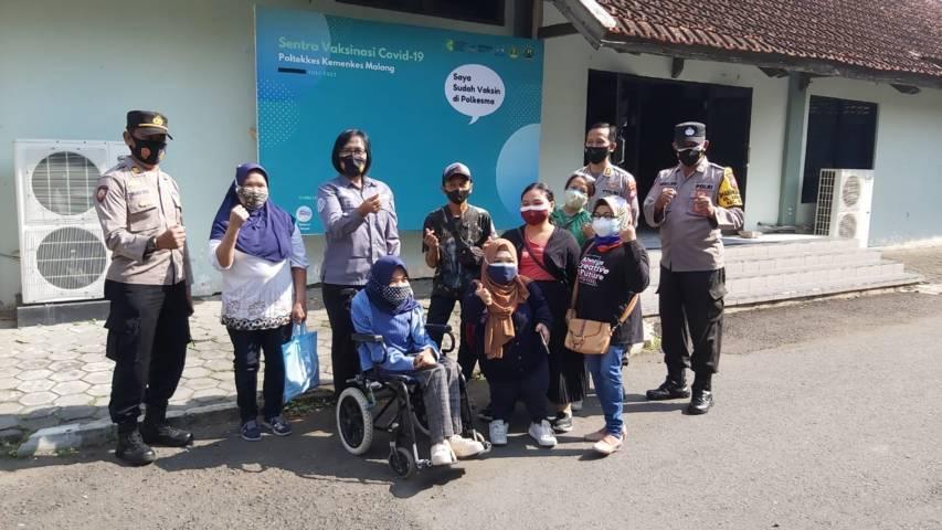 Kasubag Humas Polres Malang Kota Ipda Ni Made Seruni Marhaeni menyemangati difabel setelah vaksinasi di Polkesma, Sabtu (17/07/2021). (Foto: Dokumen/Tugu Jatim)