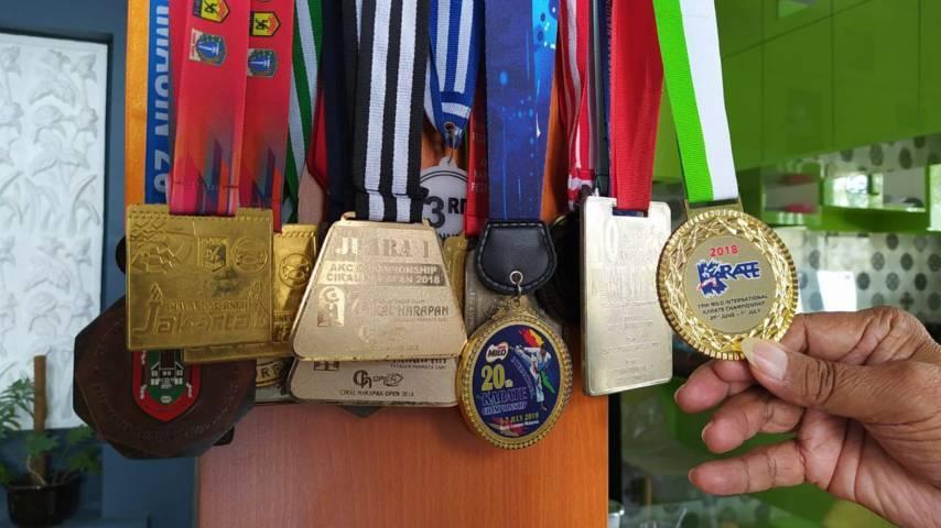 Afkar Duwera menunjukkan piala juara 1 KOSN tingkat SMP se-Kota Malang dan medali emas lainnya di rumahnya. (Foto:Azmy/Tugu Jatim)