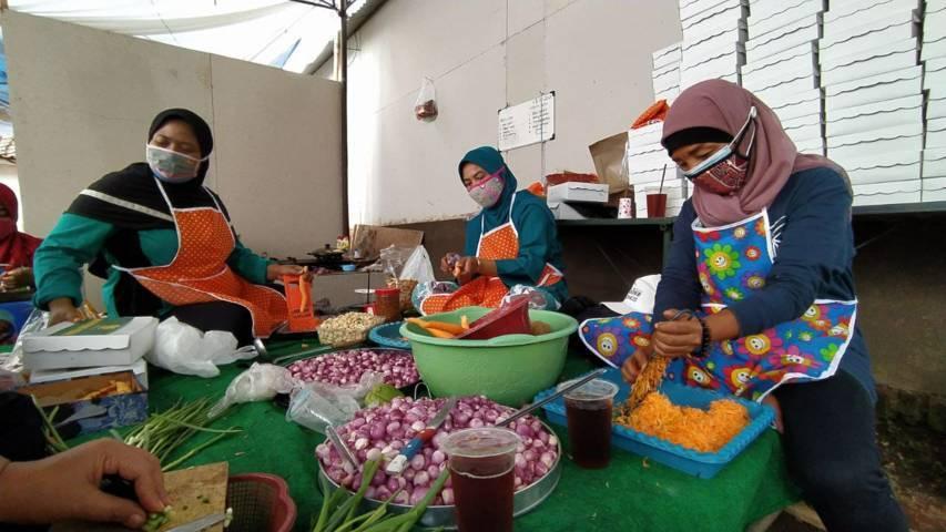 Sejumlah ibu-ibu di Kelurahan Gadang tampak sibuk menyiapkan makanan di dapur umum, Jumat (23/07/2021). (Foto:Azmy/Tugu Jatim)