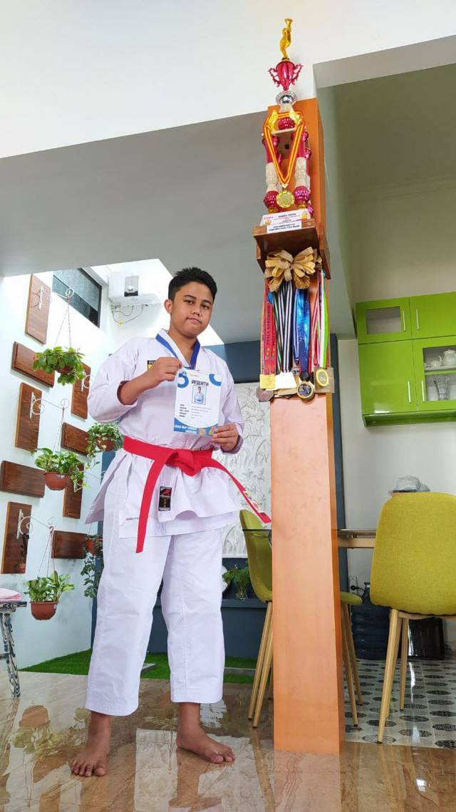 Afkar Duwera menunjukkan piagam penghargaan atas prestasinya di bidang olahraga karate. (Foto:Azmy/Tugu Jatim)
