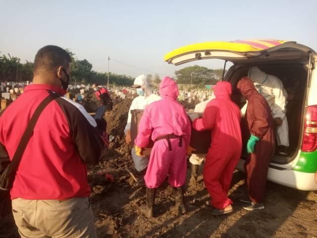 Petugas mengeluarkan peti jenazah Hamka Mudjiadi Salam dari mobil ambulans untuk dimakamkan pada Sabtu (31/07/2021). (Foto: Rangga Aji/Tugu Jatim)