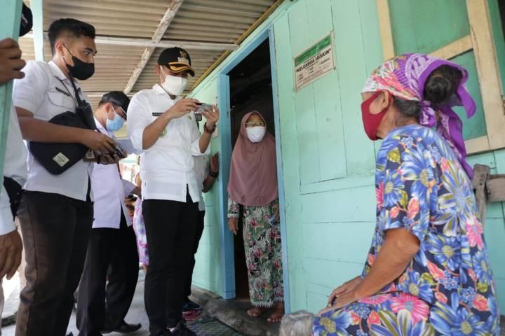 Bupati Tuban Aditya Halindra Faridzky mengecek kartu bansos salah satu KPM di Kecamatan Plumpang, Rabu (28/07/2021). (Foto: Humas Pemkab Tuban/Tugu Jatim)