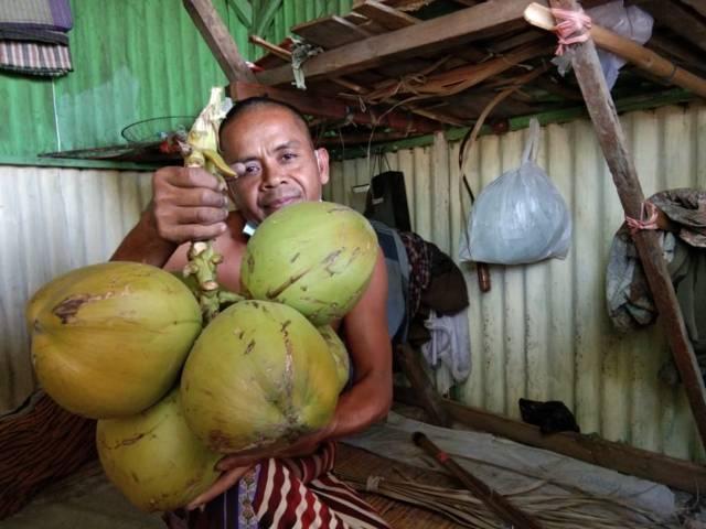 Faisol, pedagang kelapa hijau di Pasar Kota Bojonegoro saat menunjukan kelapa hijau miliknya. (Foto: Mila Arinda/Tugu Jatim)