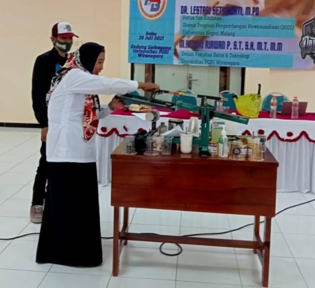 Dr Lestari Setyowati MPd langsung memberikan contoh saat pelatihan sablon cup dan botol kemasan untuk warga Kelurahan Purworejo, Pasuruan. (Foto: Dokumen/Tugu Jatim)