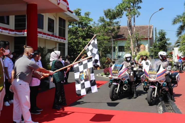 Wali Kota Batu Dewanti Rumpoko mengangkat bendera sebagai tanda pemberangkatan paket bansos dari Polres Batu. (Foto: M. Sholeh/Tugu Jatim)