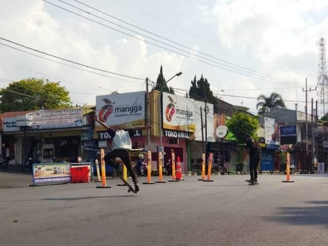 Rafli Rifai bermain skateboard dengan memanfaatkan sepinya Jalan Gajah Mada di sisi utara Alun-Alun Kota Batu. (Foto: M. Sholeh/Tugu Jatim)