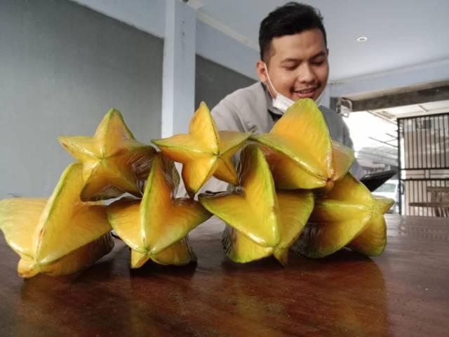 Achmad Yudho Avianto dengan hasil panen belimbing yang dibagikan kepada warga isoman, Selasa (20/07/2021). (Foto: Rino Hayyu Setyo/Tugu Jatim)