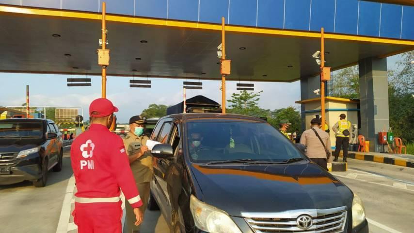 Petugas penyekatan PPKM Darurat di Exit Tol Singosari Malang, mengecek surat kelengkapan dari para pengendara. (Foto:Azmy/Tugu Jatim)