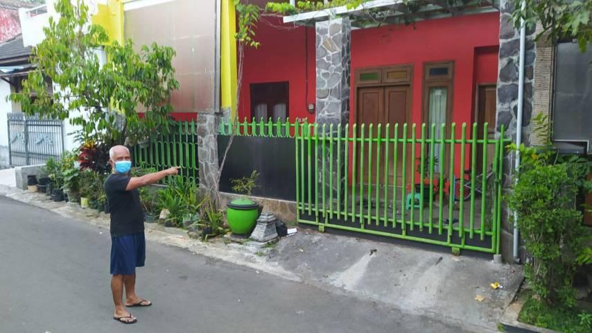 Ketua RT setempat Pudjo Leksono, 58, menunjukkan lokasi rumah 3 bocah yang menjalani isoman tanpa orang tuanya, Senin (19/07/2021). (Foto:Azmy/Tugu Jatim)