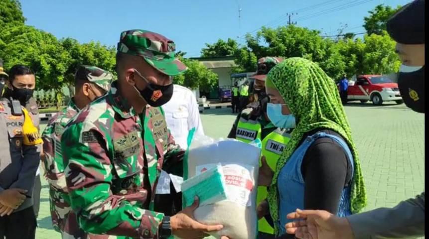 Komandan Kodim 0811 Letkol Infantri Villiala Romadon saat menyerahkan bantuan beras dan masker ke perwakilan masyarakat di Makodim 0811 Tuban. (Foto: Rochim/Tugu Jatim)