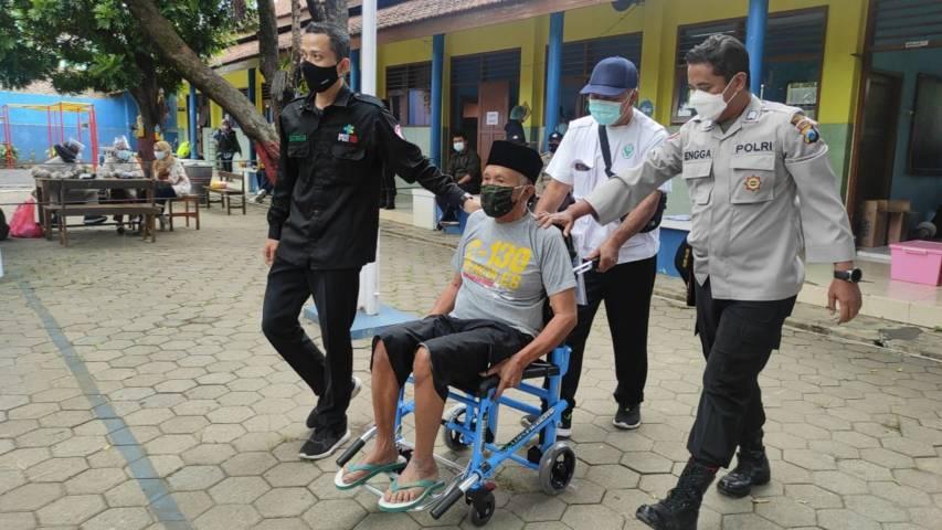 Kakek Suwadi, warga Kecamatan Pakis, Kabupaten Malang, ini dibantu petugas vaksinasi pada Sabtu siang (31/07/2021).(Foto: Rizal Adhi/Tugu Jatim)