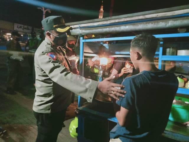 Wakapolres Malang Kompol Himawan Setiawan mengedukasi pedagang pentingnya memakai masker, Jumat (23/07/2021). (Foto: Rizal Adhi/Tugu Jatim)