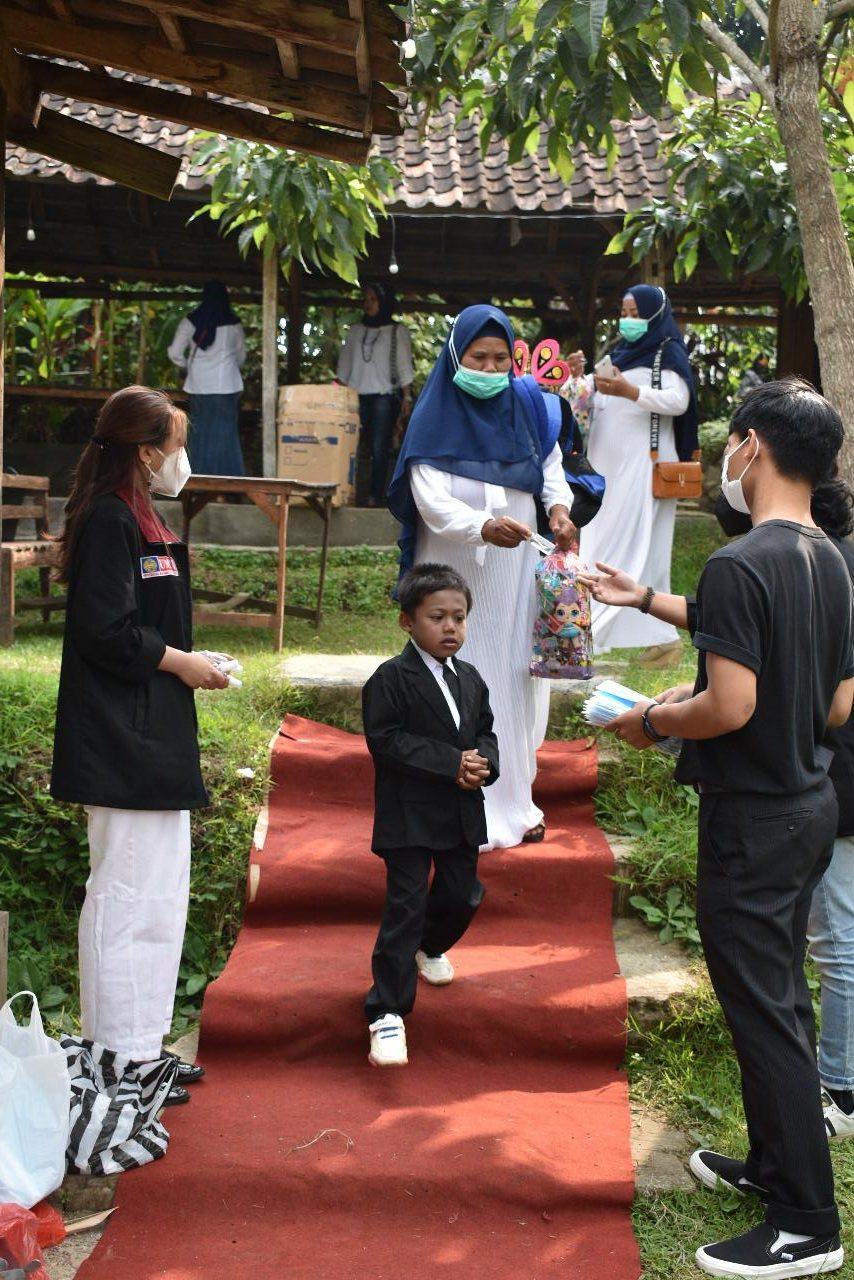 Mahasiswa PMM kelompok 69 UMM mengatur para wali murid dan siswa TK Dharma Wanita Persatuan 1, Karangploso, Kabupaten Malang, untuk menerapkan prokes ketika acara wisuda. (Foto: Dokumen/Tugu Jatim)
