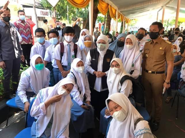 Gubernur Jawa Timur Khofifah Indar Parawansa (memakai rompi) dan Bupati Tuban Aditya Halindra Faridzky (kanan) foto bersama para siswa MAN 1 Tuban yang antusias mengikuti vaksinasi Covid-19. (Foto: Humas Kemenag/Tugu Jatim)