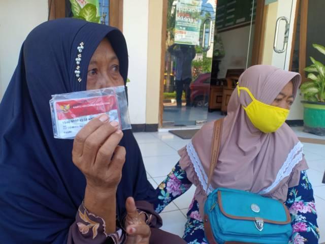 Pasri, salah satu penerima bansos sembako, menunjukkan kartu merah putih atau Kartu Keluarga Sejahtera (KKS) di kantor Dinsos Tuban, Rabu (28/07/2021). (Foto: Rochim/Tugu Jatim)