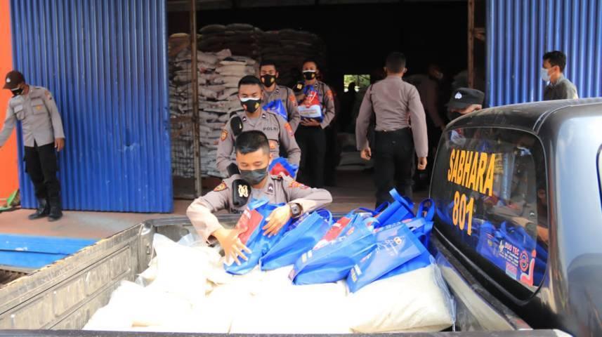 Anggota Polres Tuban memuat bantuan beras kemasan 5 kilogram untuk warga pada Senin (19/07/2021). (Foto: Humas Polres Tuban/Tugu Jatim)