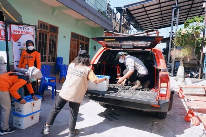 Personel BPBD Kota Kediri ketika mengirimkan paket permainan untuk anak-anak terdampak pandemi di daerah yang terkena lockdown. (Foto: Rino Hayyu/Tugu Jatim)