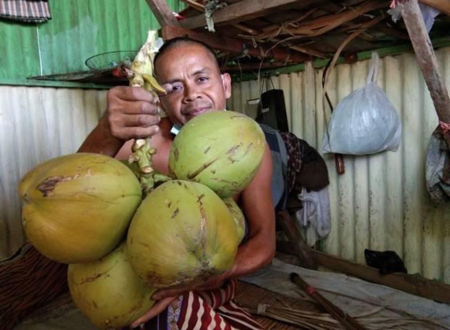 Faisol, penjual kelapa di Pasar Kota Bojonegoro saat menjelaskan kenaikan harga kelapa hijau, Kamis (28/07/2021). (Foto: Mila Arinda/Tugu Jatim)