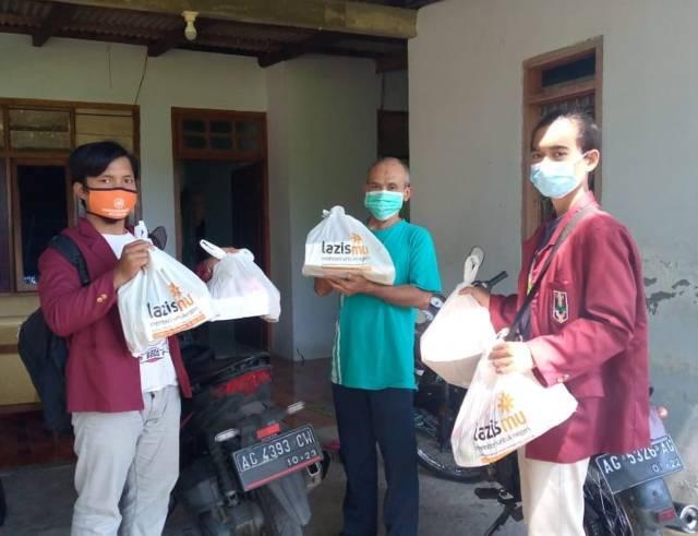 Lazismu dan IMM Kediri yang saling berkolaborasi membantu warga yang tengah menjalani isolasi mandiri dengan memberikan paket bantuan makanan dan suplemen vitamin, Minggu (25/7/2021). (Foto: Rino Hayyu/Tugu Jatim)