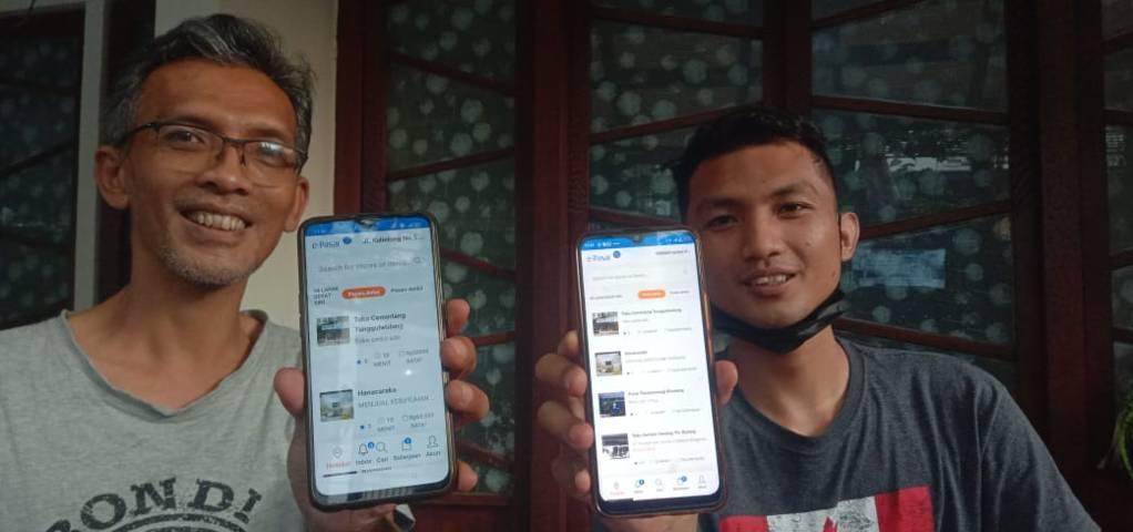 Wakil Ketua Bidang Perdagangan dan Distribusi KADIN Kota Malang, Dicky Sulaiman (kiri) menunjukkan aplikasi e-Pasar Malang. (Foto: Dokumen) tugu jatim