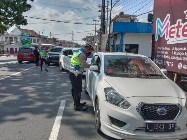 Petugas Polres Batu memeriksa kelengkapan syarat surat perjalanan pengendara dari luar Kota Batu di hari kedua PPKM Darurat, Minggu Minggu (4/7/2021). (Foto: M Sholeh/Tugu Malang/Tugu Jatim)