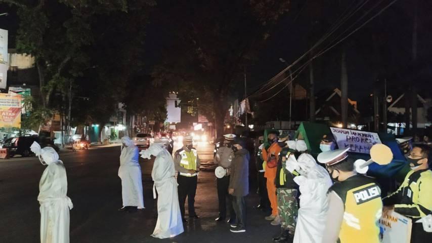 Petugas gabungan di Kota Malang saat sosialisasi bahaya Covid-19 selama masa PPKM Darurat menggunakan keranda mayat dan sosok pocong, Senin (5/7/2021) malam. (Foto: M Ulul Azmy/Tugu Malang/Tugu Jatim)