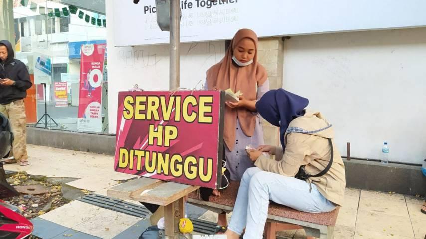 Para penyedia jasa layanan servis HP yang menawarkan jasa mereka di pinggir jalan demi mencari rezeki. (Foto: M Ulul Azmy/Tugu Malang/Tugu Jatim)