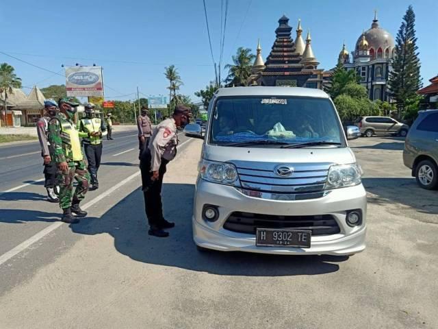 Jajaran petugas gabungan terlihat menghentikan kendaran yang masuk wilayah Tuban di perbatasan Jatim-Jateng dengan memeriksa kelengkapan dokumen syarat perjalanan di setiap kendaraan. (Foto: Dokumen/Humas Polres Tuban)