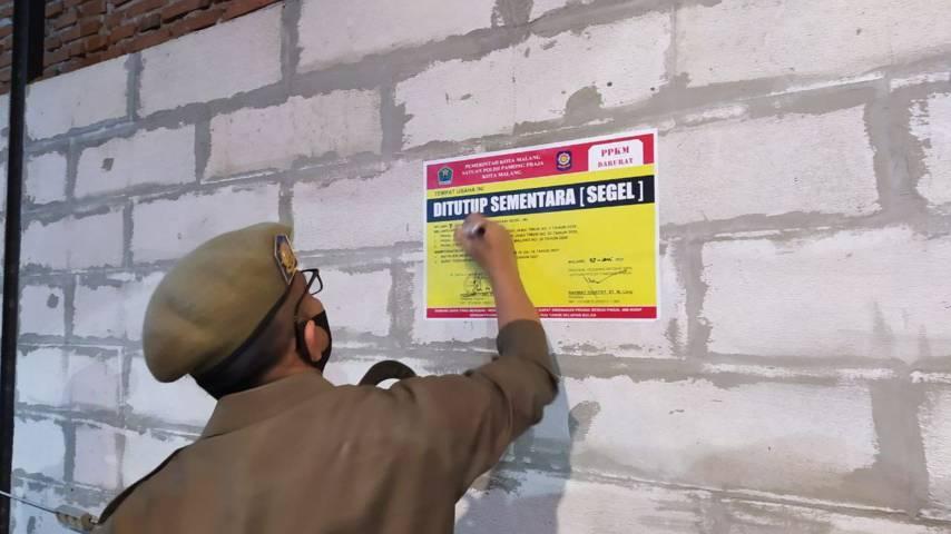 Kabid Tratibum Satpol PP Kota Malang, Rahmat Hidayat menempel stiker segel penutupan sementara di kafe yang kedapatan melayani dine-in, Rabu (7/7/2021) malam. (Foto: M Ulul Azmy/Tugu Malang/tugu Jatim)