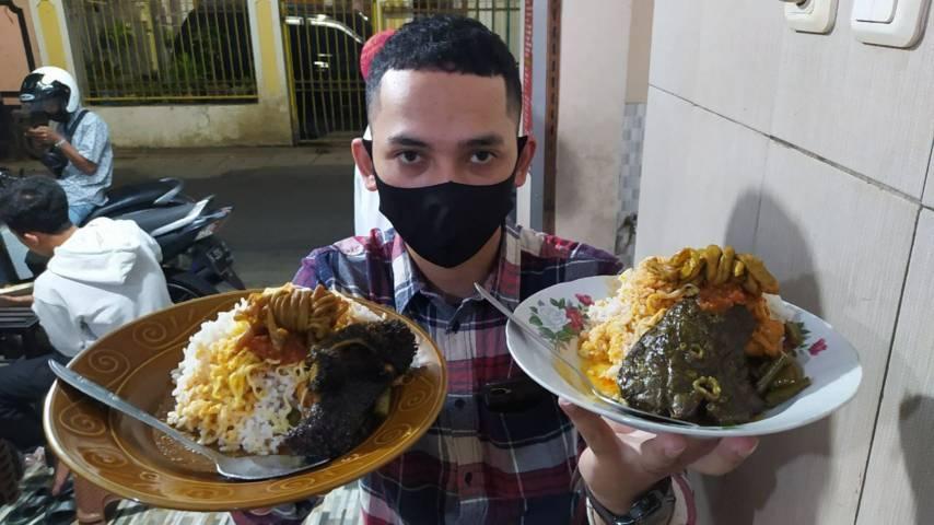 Seorang pembeli kuliner Sego Penjara tengah mengangkat piring dan menunjukkan menu yang melegenda. (Foto: M Ulul Azmy/Tugu Malang/Tugu Jatim)
