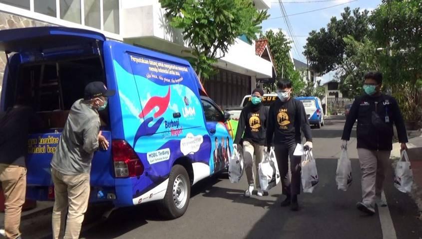 Mahasiswa UMM tampak membawa paket sembako bantuan logistik yang dibagikan untuk pasien Covid-19 yang tengah isoman dan juga PKL. (Foto: Rubianto/Tugu Malang/Tugu Jatim)