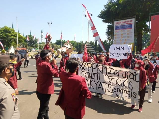 Anggota Ikatan Mahasiswa Muhammad (IMM) Tuban menggelar aksi di depan Gedung Pemkab Tuban, Kamis (12/08/2021) untuk menuntut PPKM dievaluasi dan dikaji ulang. (Foto: Rochim/Tugu Jatim)