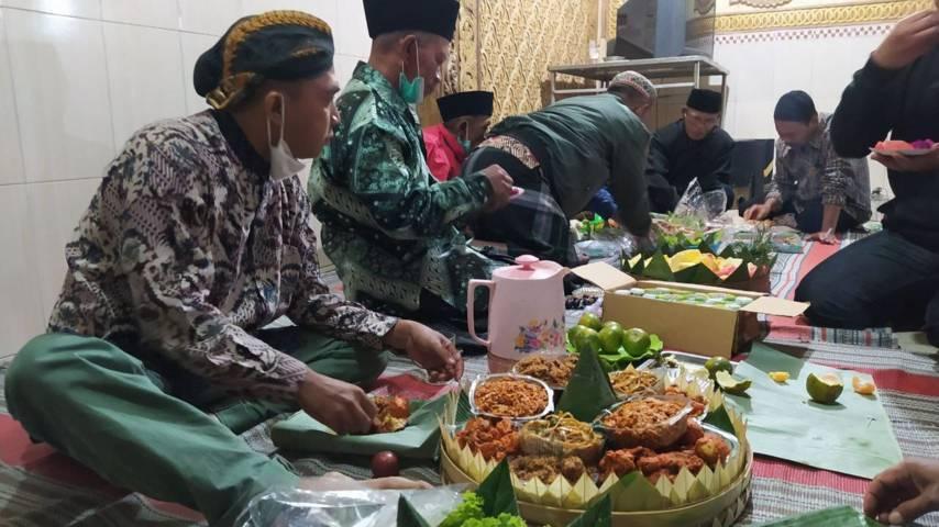 Warga makan bersama usai menggelar selamatan tolak bala pada Kamis Legi (08/07/2021). (Foto:Azmy/Tugu Jatim)