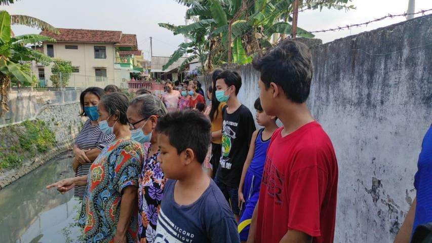 Warga Kelurahan Banjaran, Kota Kediri, ini melihat evakuasi mayat bayi yang mengapung di Sungai Kresek, Kota Kediri, Sabtu (14/08/2021).(Foto: Rino Hayyu Setyo/Tugu Jatim)