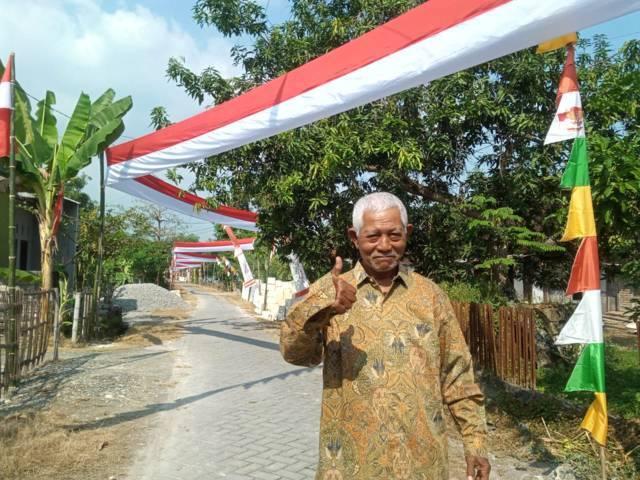 Slamet, Ketua RT Dusun Gumelem, Desa Bogangin, Kecamatan Sumberrejo, Kabupaten Bojonegoro, saat foto berlatar belakang pembentangan bendera Merah Putih sepanjang 500 meter pada Selasa (10/08/2021). (Mila Arinda/Tugu Jatim)